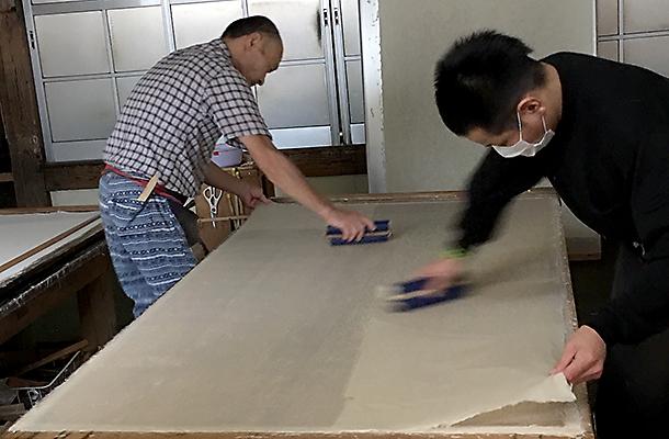 ヘラで気泡を抜きながら乾燥用の干し板に平坦に貼りつけ